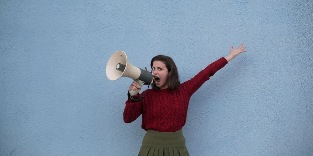 angry-woman-yelling-into-loudspeaker-on-blue-background-3978388.jpg
